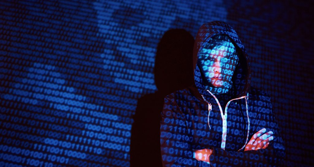 A hooded hacker with his face obscured by website code
